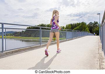 Slim woman running outdoor on bridge over a lake
