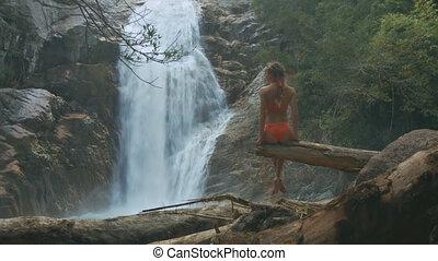 Slim Woman Sits on Tree Takes Pleasure in Waterfall