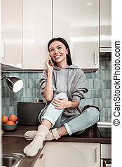 Slim woman sitting in the kitchen and speaking on the phone
