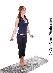 Slim woman standing doing yoga