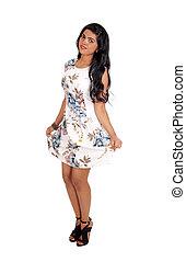 Slim woman standing in dress.