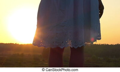 Slim Woman Turns The Hem of Her White Folk Dress at Nice Sunset