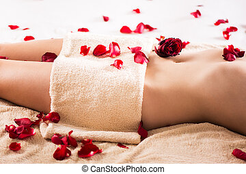 Beautiful female body covered with a towel and petals of roses.