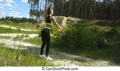 slim young blonde woman in sports uniform squats outdoors