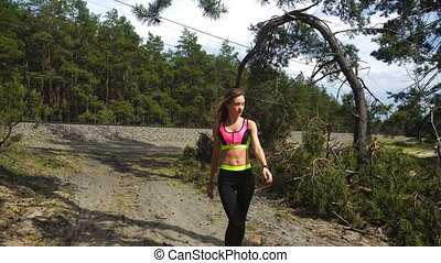 slim young blonnde in sports uniform walks down the forest...