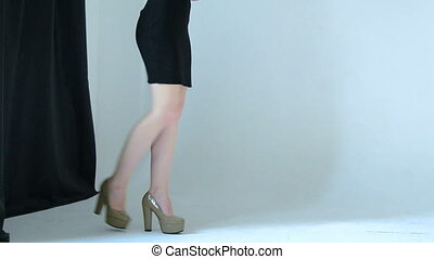 Slim young girl in a black dress and heeled shoes walks