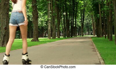 Slim young girl in shorts rollerblading