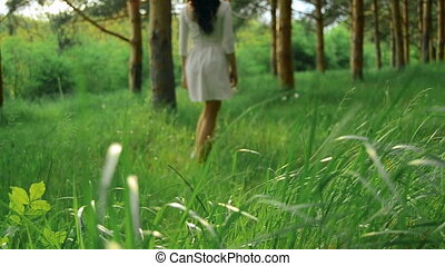 slim young girl in white dress walks in the green wood -...