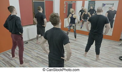 Slim young guys worming up on aerobics class at gym following the exercises of a woman fitness instructor