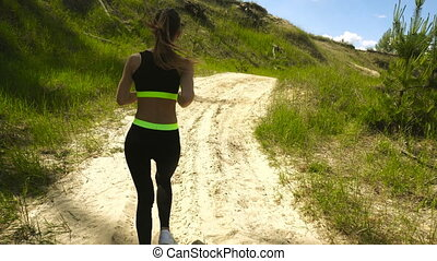 slim young lady in sports uniform running around outdoors