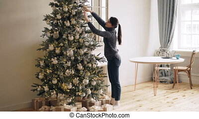 Slim young lady is decorating New Year tree touching shiny balls and lights standing indoors at home alone. Christmas decorations, interior and people concept.