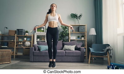 Slim young sportswoman jumping rope in apartment focused on...