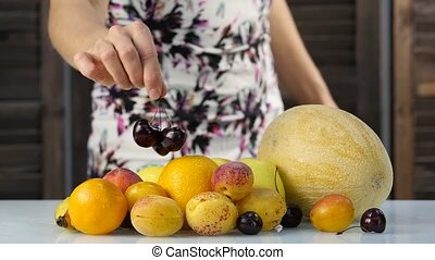 Slim young woman choosing fruits. Healthy eating. Weight loss and dieting concept. slow motion