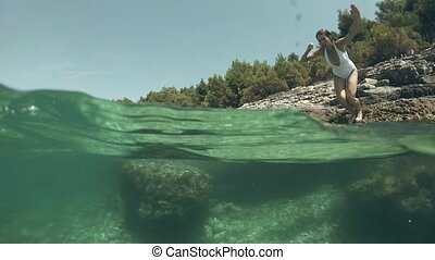 Slim young woman diving into the sea, underwater shot -...