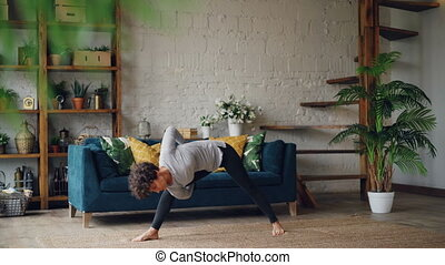 Slim young woman is doing sequence of hatha yoga asanas alone at home enjoying personal training and solitude. Active youth and self-development concept.