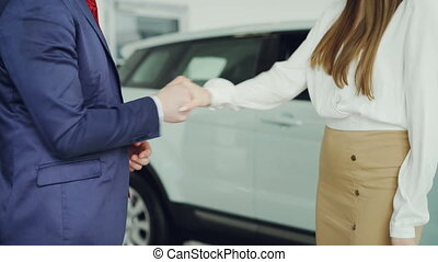 Slim young woman is getting car keys from salesman in suit then shaking hands with him to celebrate successful deal standing beside luxurious new automobile.