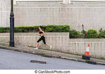 Slim young woman running uphill on sidewalk of city street....