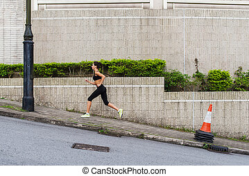 Slim young woman running uphill on sidewalk of city street. ...