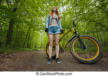 Slim young woman standing in the green woods with fat bike