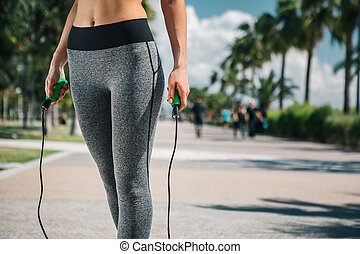 Slim young woman using a jump rope