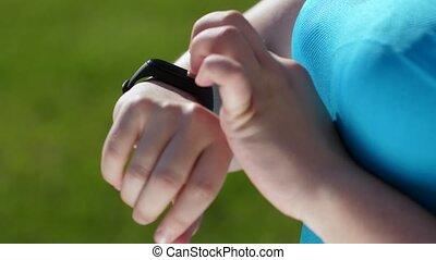 Slimming woman jogger using fitness bracelet - Close-up of ...