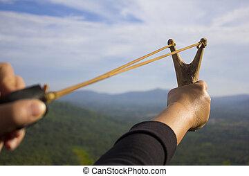 Sling shot - Hand pulling sling shot preparing to shot the...
