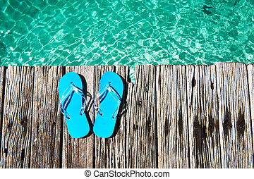 Slippers at jetty by the sea