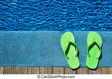 Slippers by a swimming pool - Green slippers by a swimming...