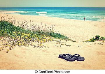Slippers on the background of the beautiful beach and the sea. In the warm colors.