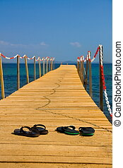 slippers on wooden peer with blue sea