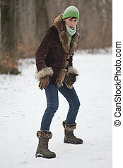 slippery snowy road - woman goes with great care on slippery...