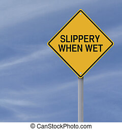 Slippery When Wet road sign against a blue sky background