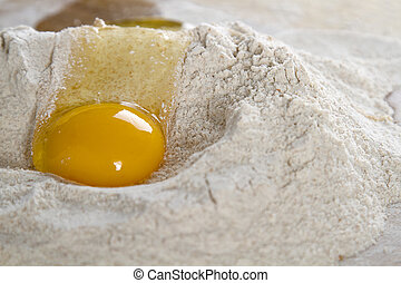 slippy egg - cracked chicken egg flowing in a nest of flour