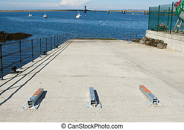 An open concrete slipway with security posts laying on the floor a metal hand rail on the edge, lobster pots against a wall and a blue sea beyond.