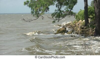 Waves crashing onto a rocky river shore in slow motion.