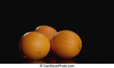Slo-motion oranges falling on dark background with copy space at the top