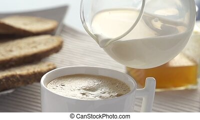 Slomo adding milk in coffee - Slow motion adding milk in...