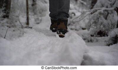 slomo clip of closeup female warm winter boots walking in...