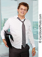 Sloppy businessman with briefcase looking at camera
