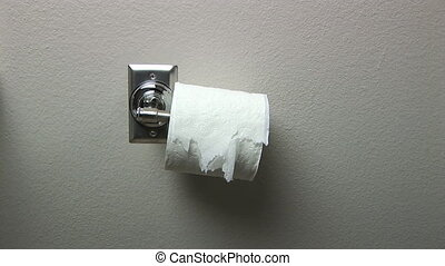 Ripped toilet paper roll hanging unevenly