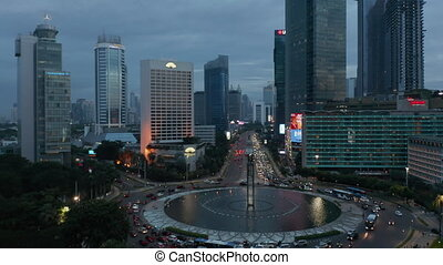 Slow aerial dolly shot of busy traffic on a roundabout in modern city center in Jakarta, Indonesia 4K