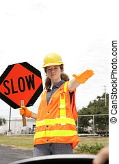 Slow Behind the Wheel - A road crew member holding a sign & ...