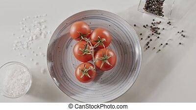 Slow circular movement, top view video in 4K, close-up of cherry tomatoes on a blue ceramic plate on a white kitchen table, pepper and salt in a glass jar.