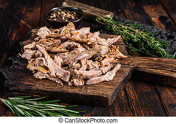 Slow cooked puilled pork meat on a wooden board with butcher cleaver. Dark wooden background. Top view