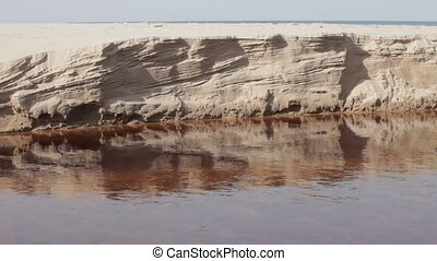 Eroded sand riverbank - Slow flowing river with Eroded sand...