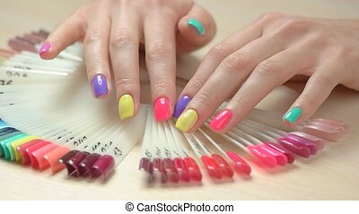 Slow maotion hands choosing nail color. Close up young woman...