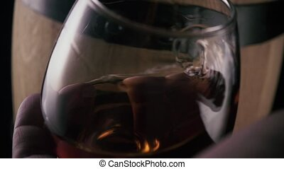 Slow mo. A glass of cognac in the hand in motion