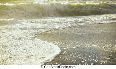 Slow mo foam from the wave rolling on the sand - Slow mo...