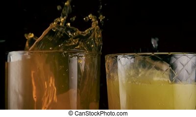 Slow mo. In two glasses with drinks falls the ice