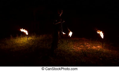 Close-up. Slow motion of a young man in black clothes in the dark depicts a rotating burning ball poi. Meditation in motion. Calm and unwavering. Work with fire. Low key. Fire show